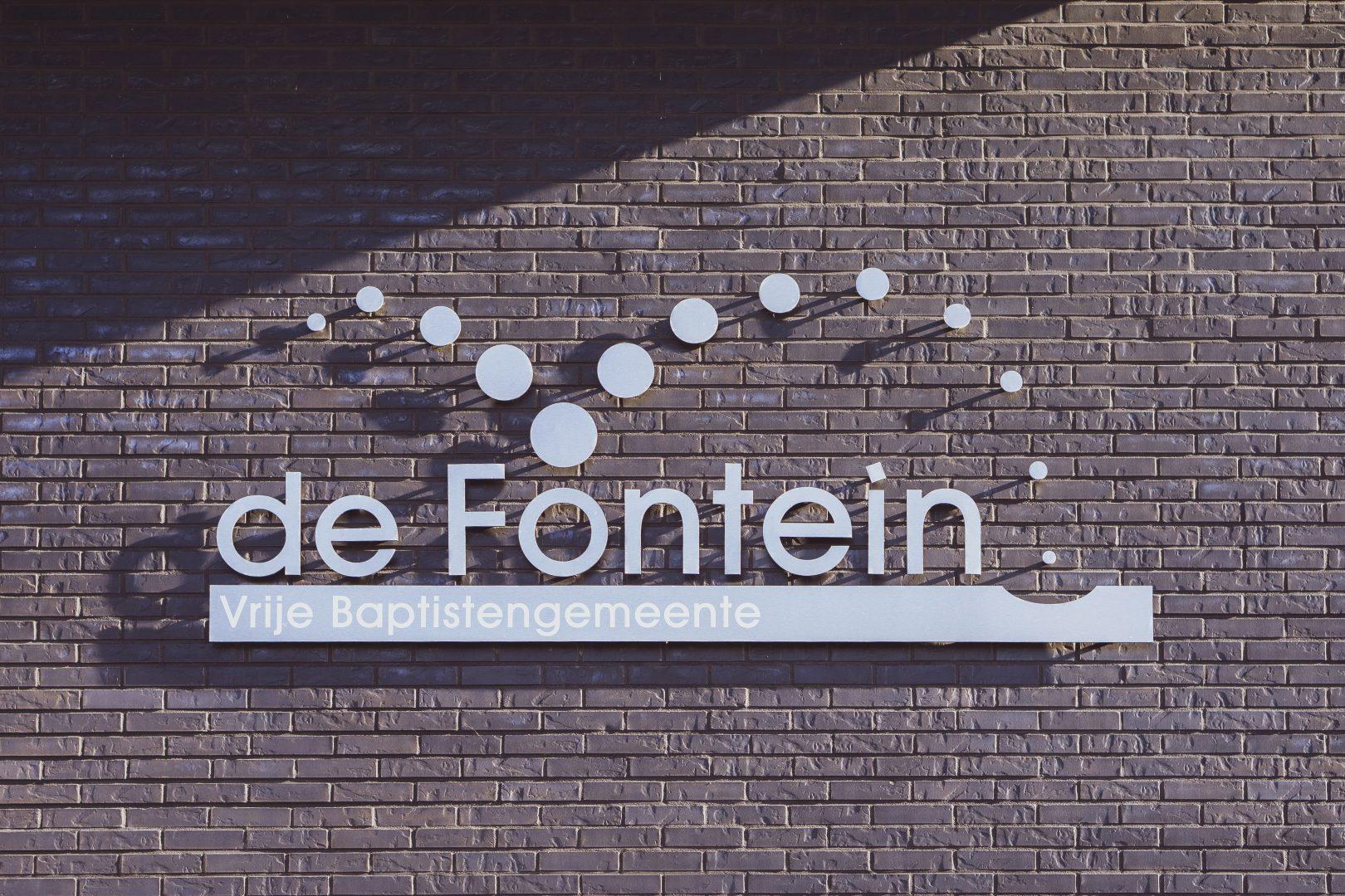 """Logo """"Vrije Baptistengemeente de Fontein"""" op muur"""