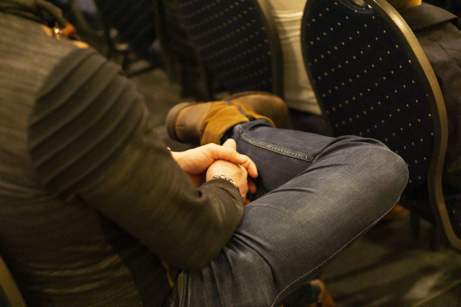 Man op stoel – gevouwen handen
