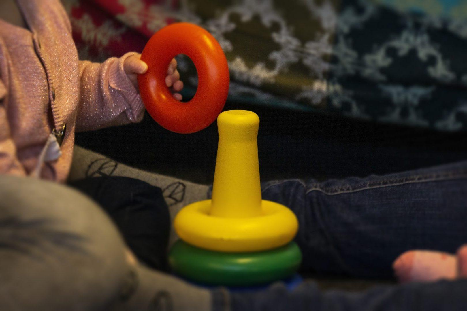 Baby met speelgoed ring